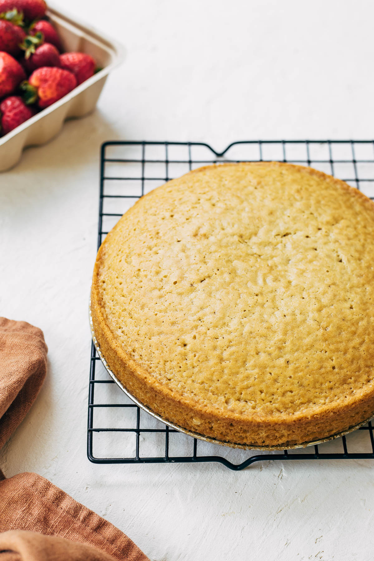 A baked round cake on a square cooling rack.