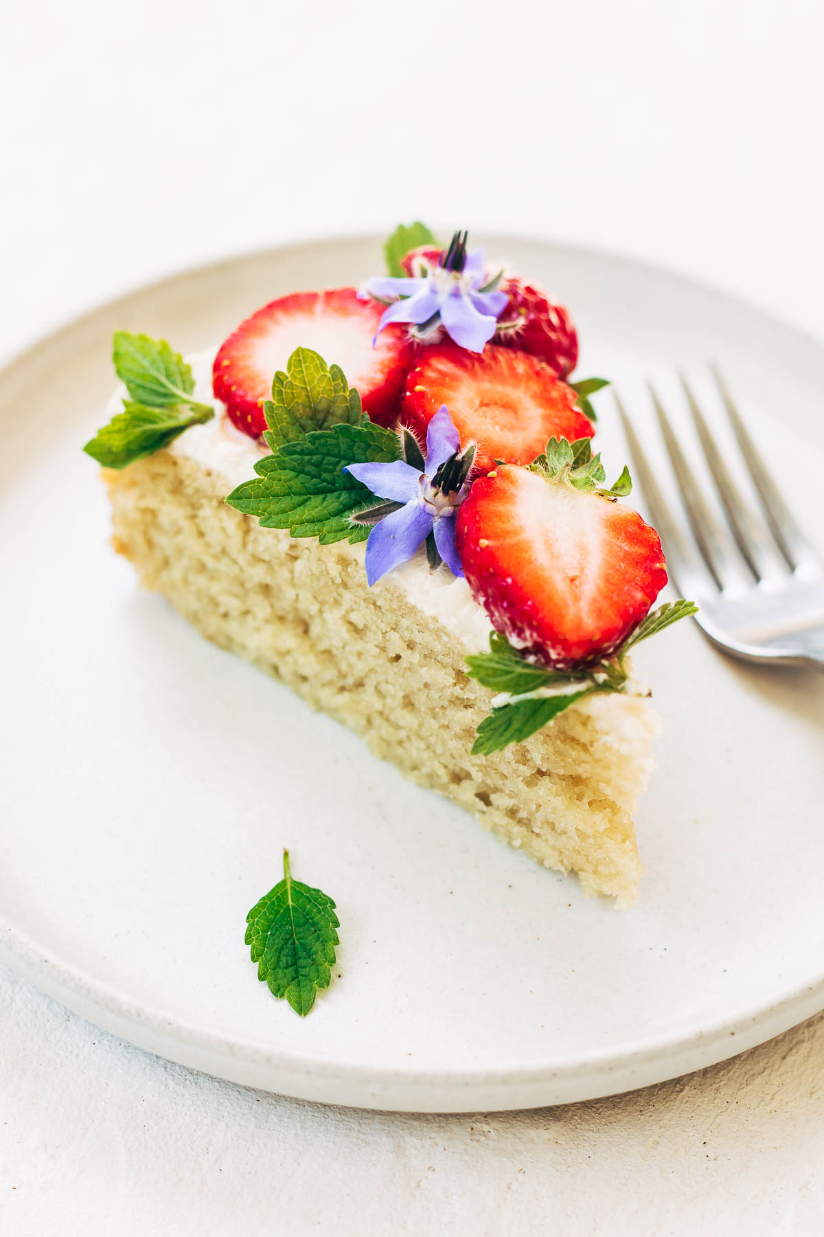 A slice of vanilla cake with white buttercream, strawberries, and edible flowers/herbs.