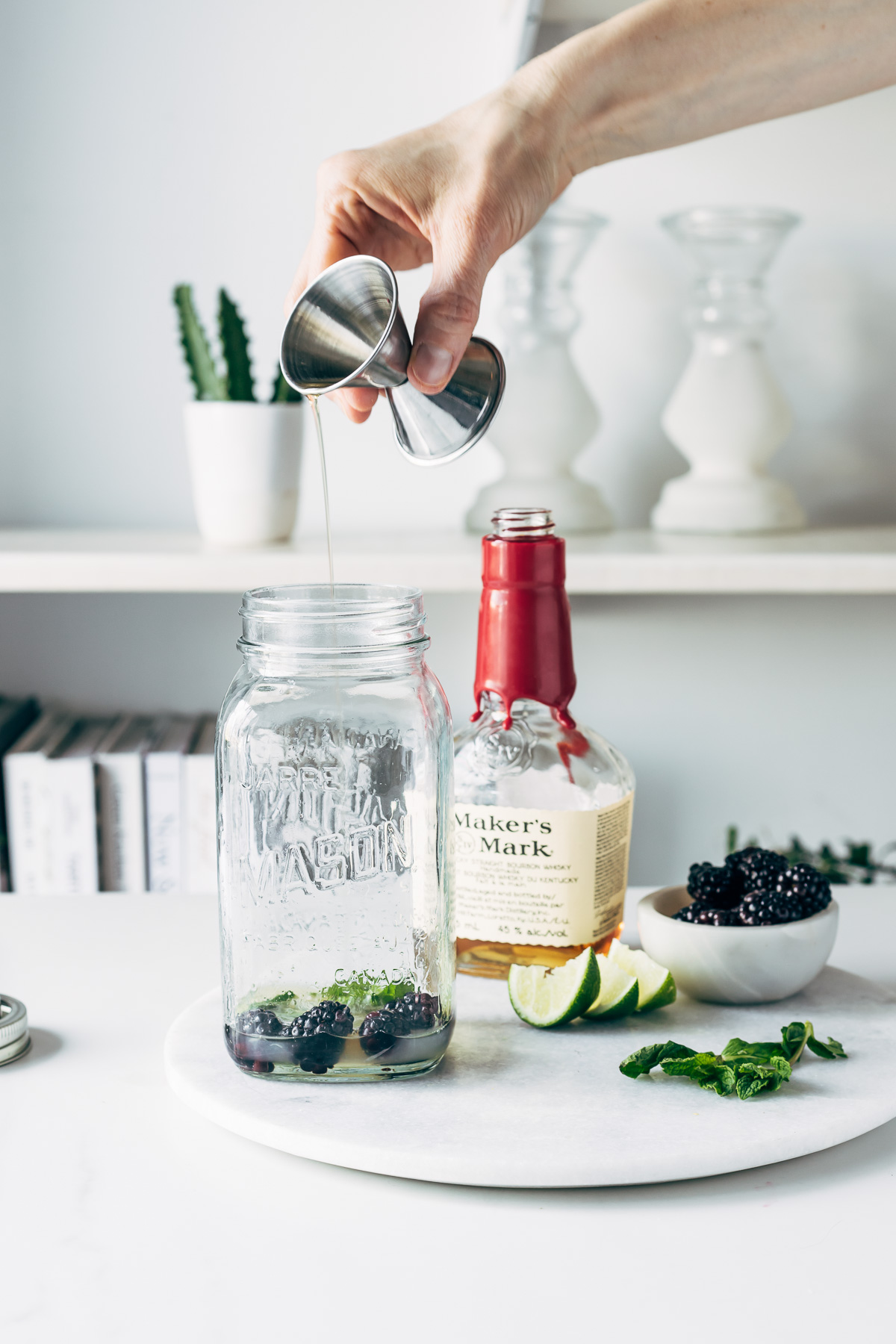 A person pouring bourbon into a mason jar with blackberries and mint leaves.