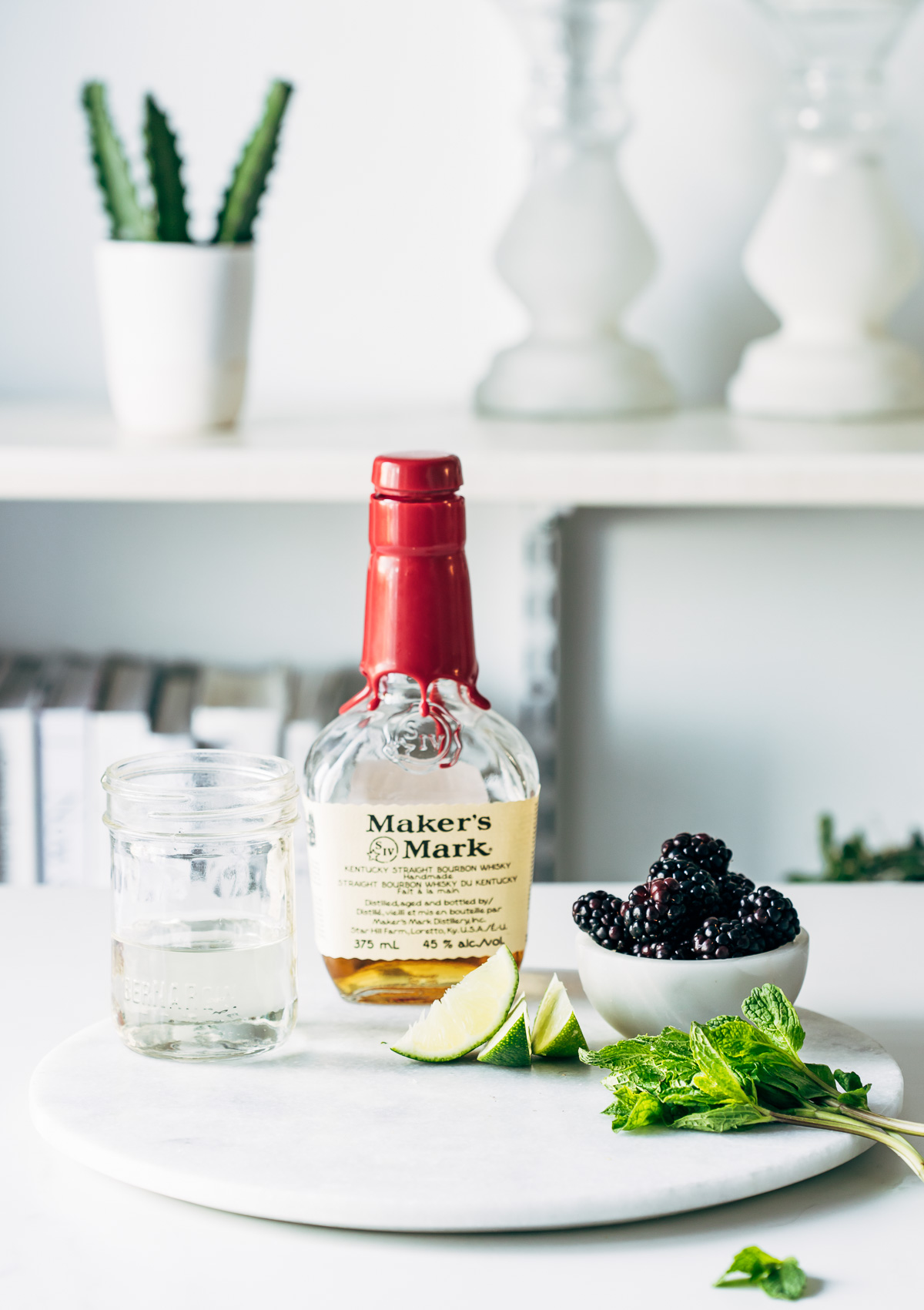Ingredients to make a blackberry bourbon smash on a round marble board.