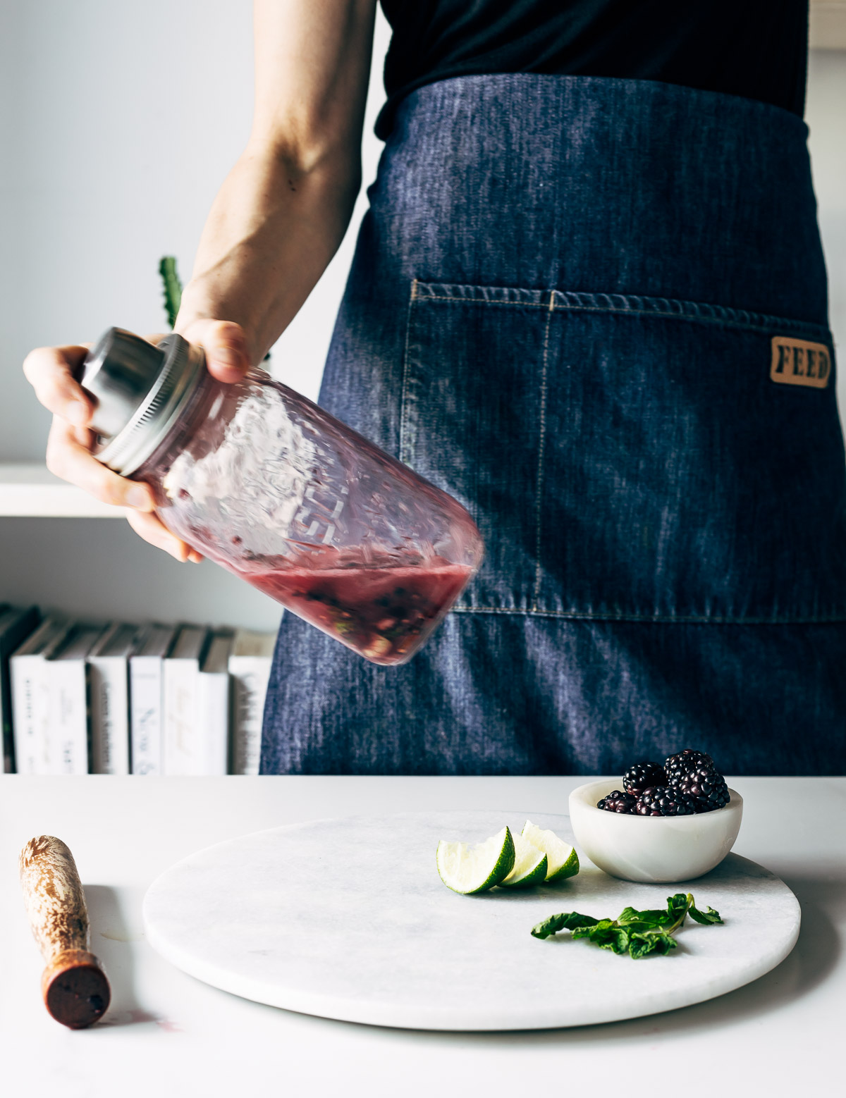 A person in a black shirt and denim apron shaking dark purple liquid in a Mason jar cocktail shaker in front of a table with a marble board, wooden muddler, cut limes, mint leaves, and a small bowl of blackberries.