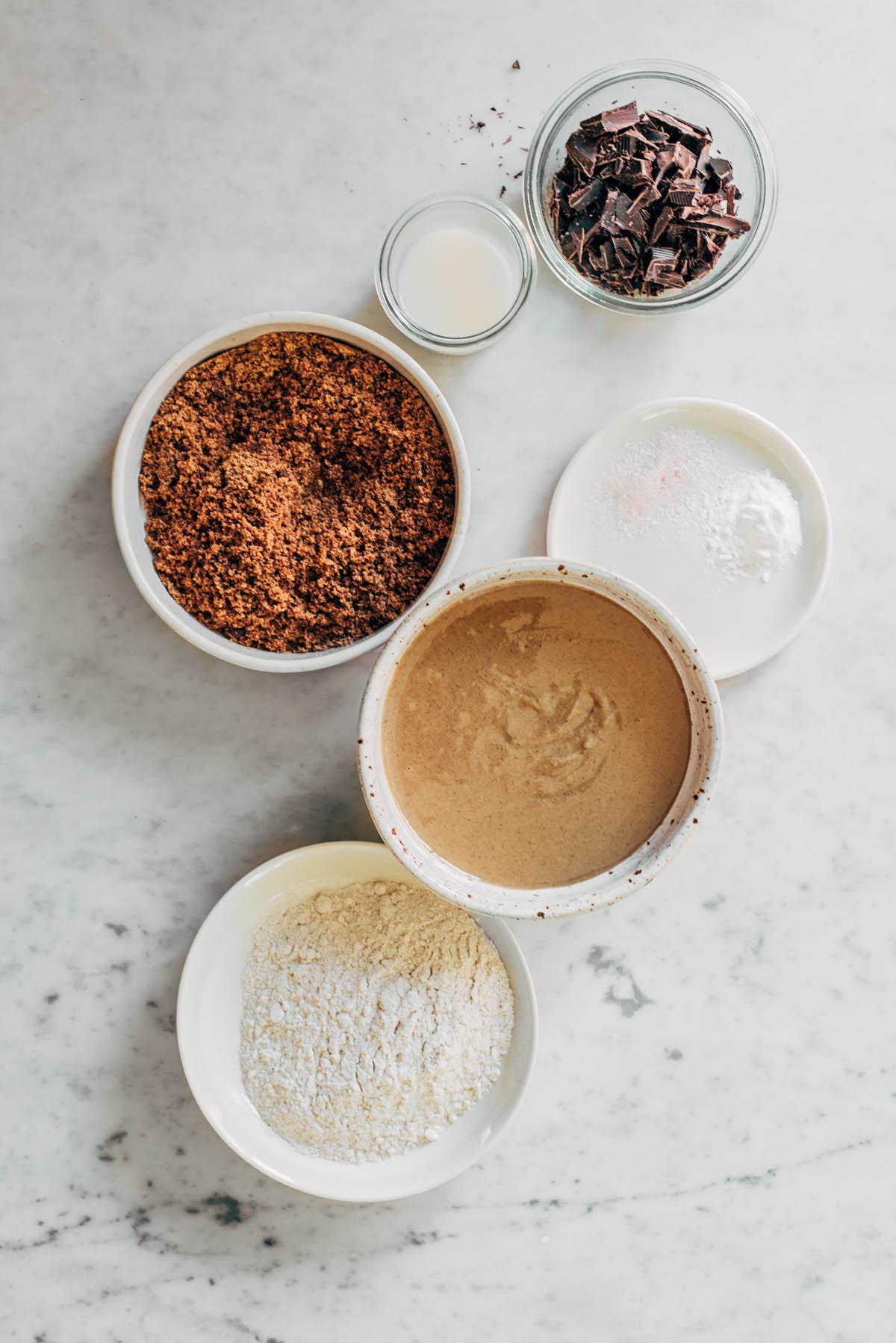 Chocolate tahini cookie ingredients: tahini, oat flour, chocolate chunks, brown sugar, salt, baking soda, and milk.