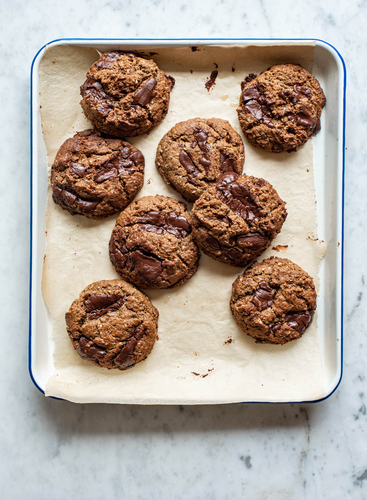 Chocolate chunk tahini cookies on a parchment lined baking tray.
