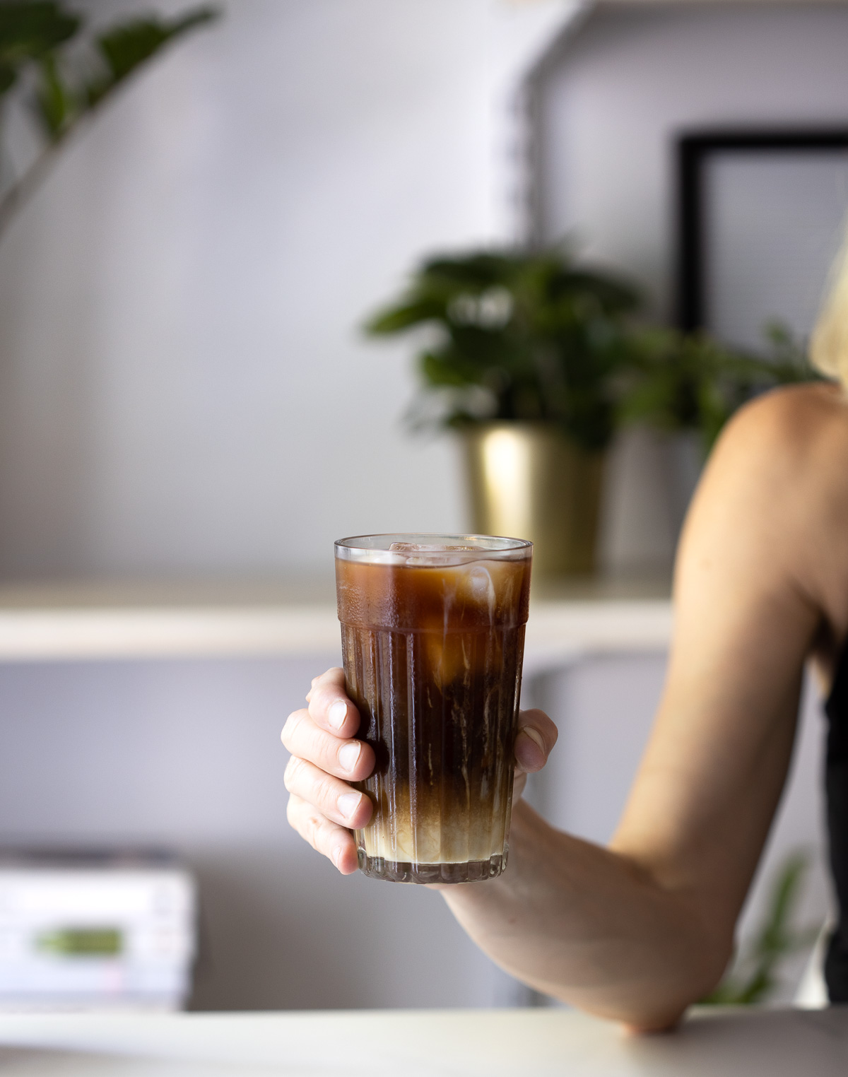 A woman's arm and hand holding a glass of iced milky coffee.