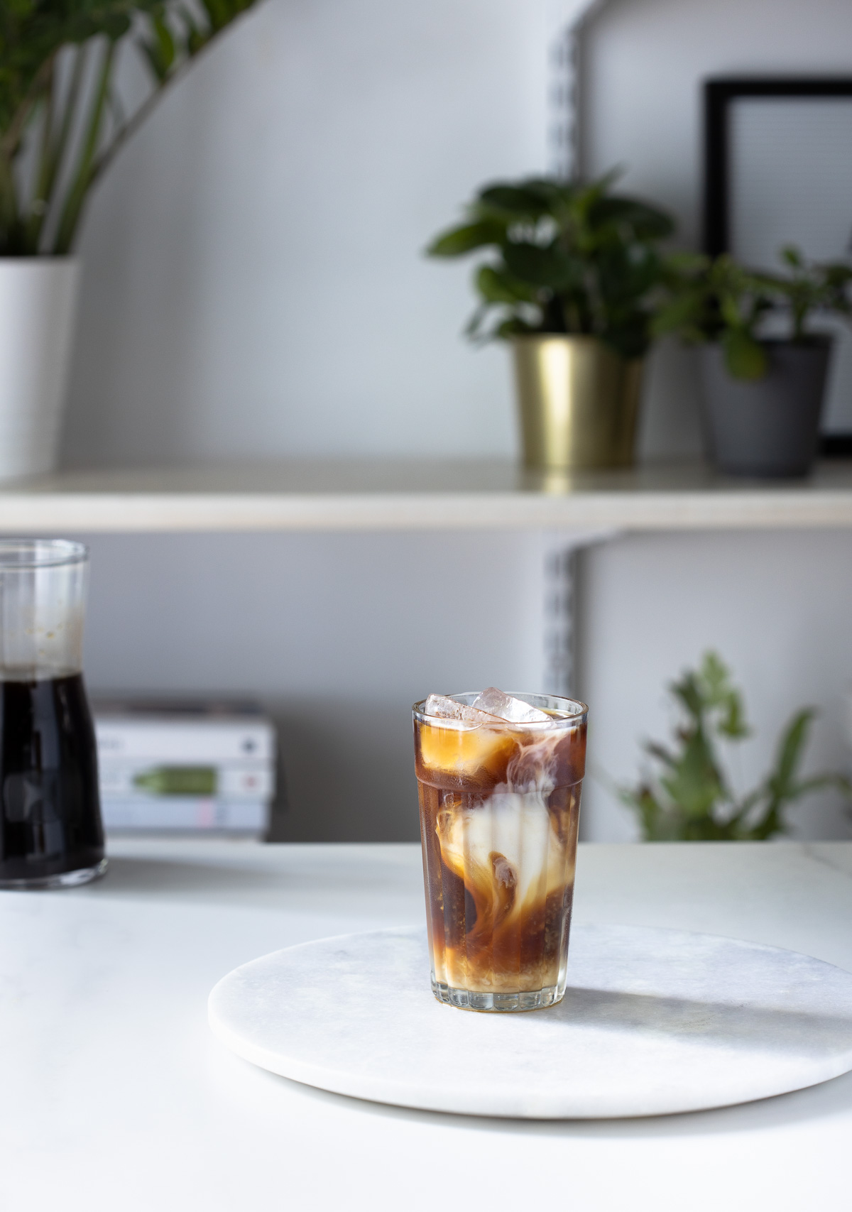 A glass of iced coffee made with cold brew sitting on a round marble board in a white kitchen.