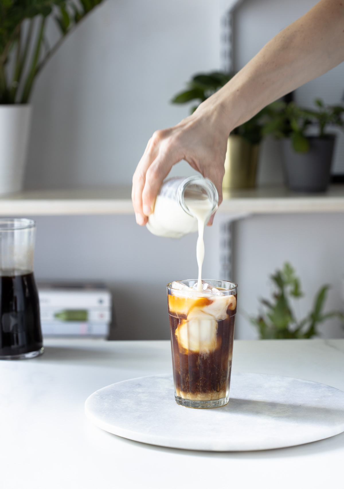 A woman's hand pouring milk into a glass of cold brew coffee with ice.