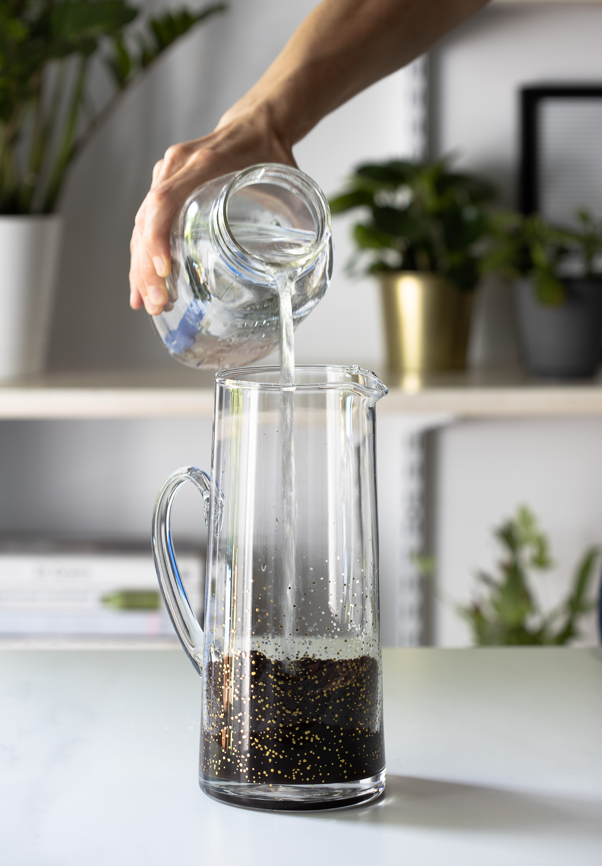 A hand pouring water into a glass pitcher with coarse ground coffee inside.