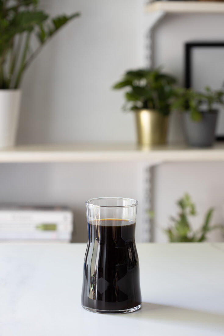 A small glass canister of cold brew coffee.