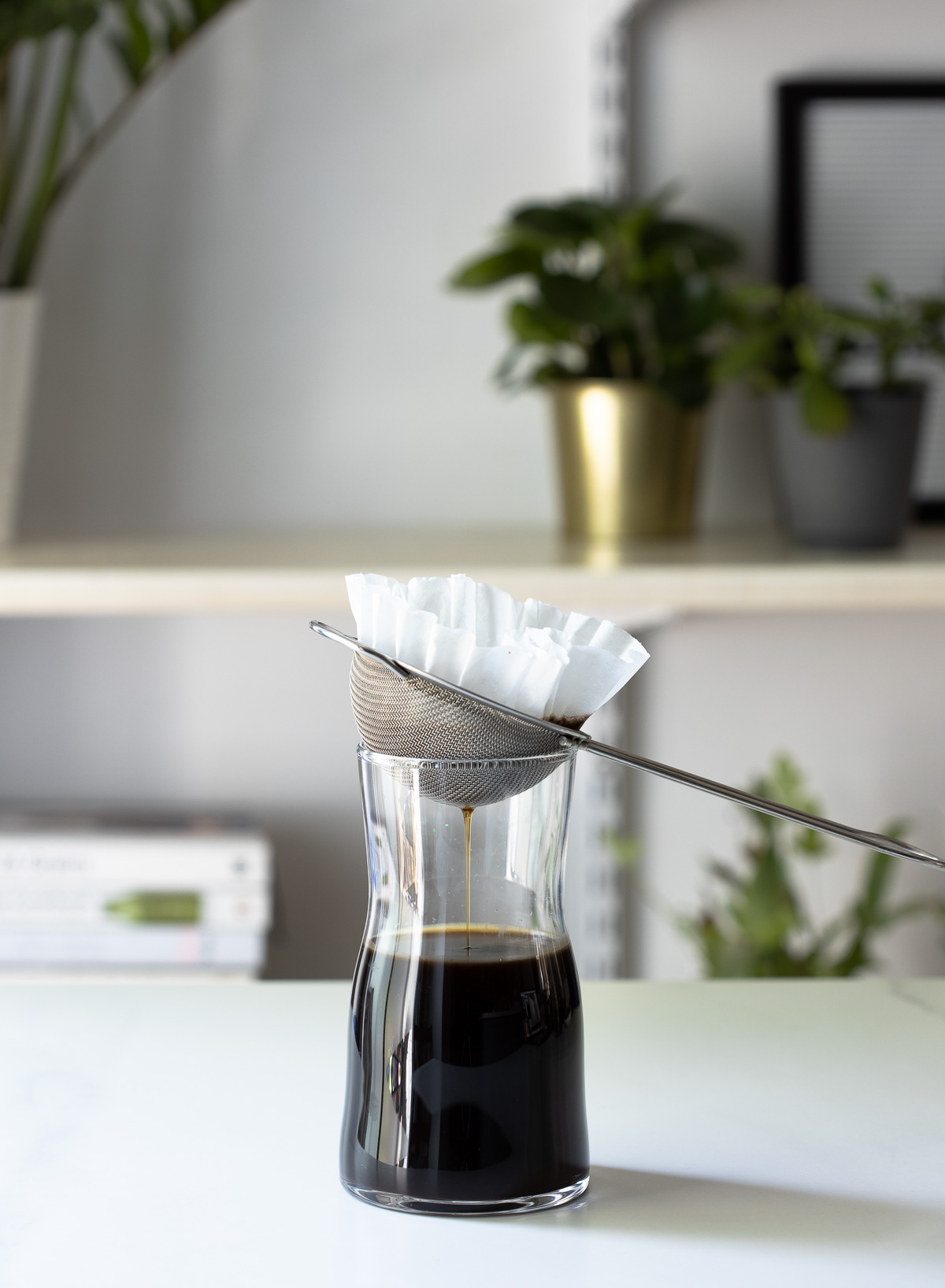 Cold brew coffee dripping through a sieve lined with a coffee filter into a tall glass canister.
