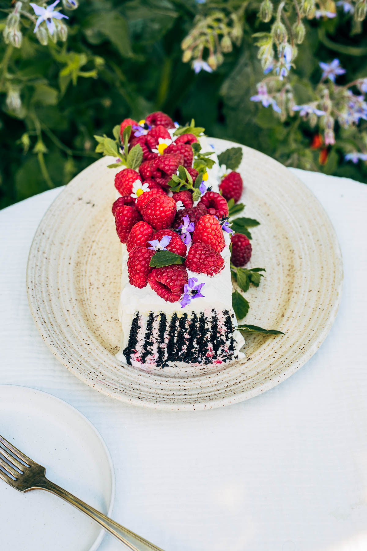 Icebox cake topped with berries and flowers, one slice removed.