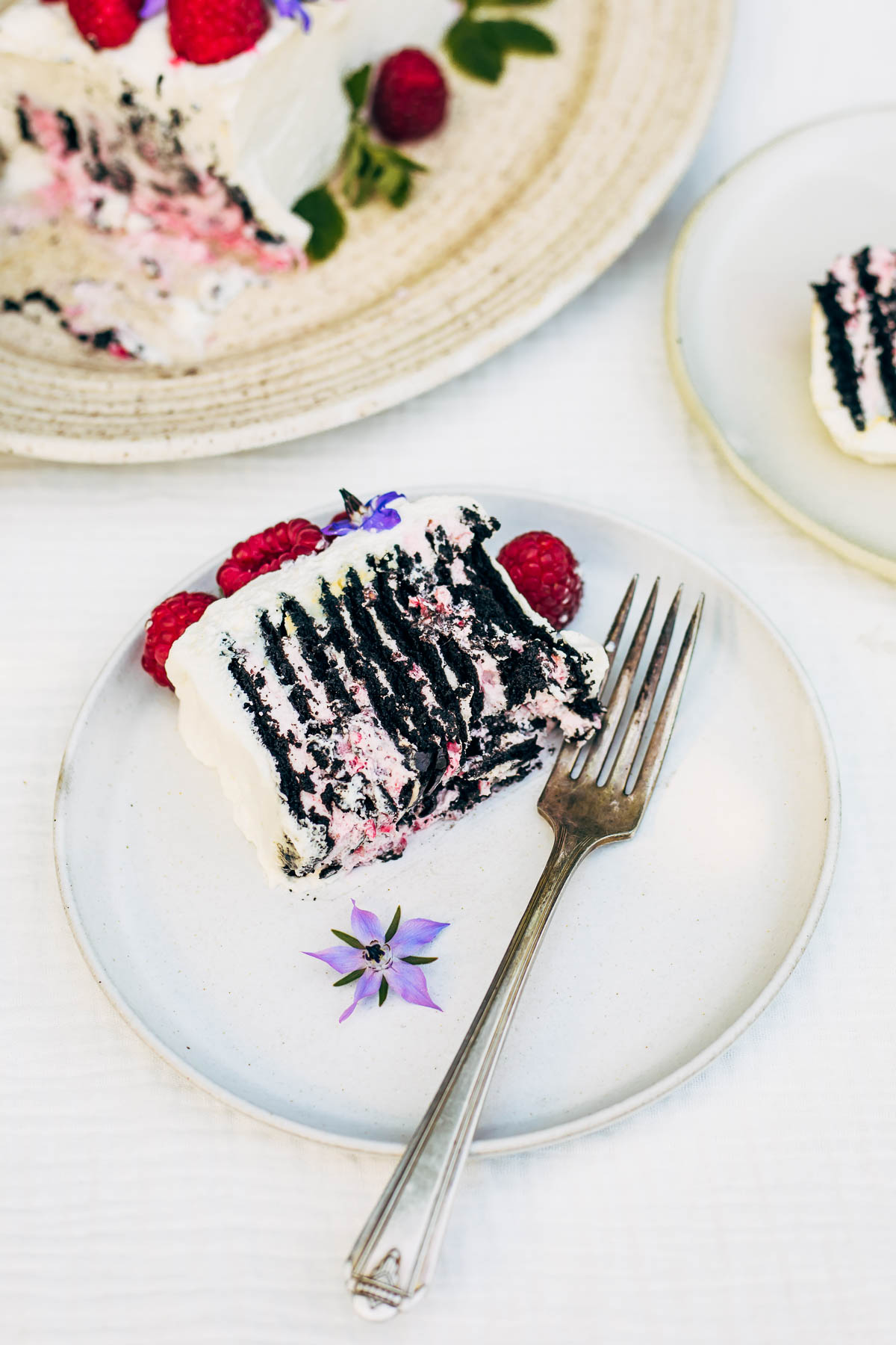 Slices of icebox cake with raspberries on plates.