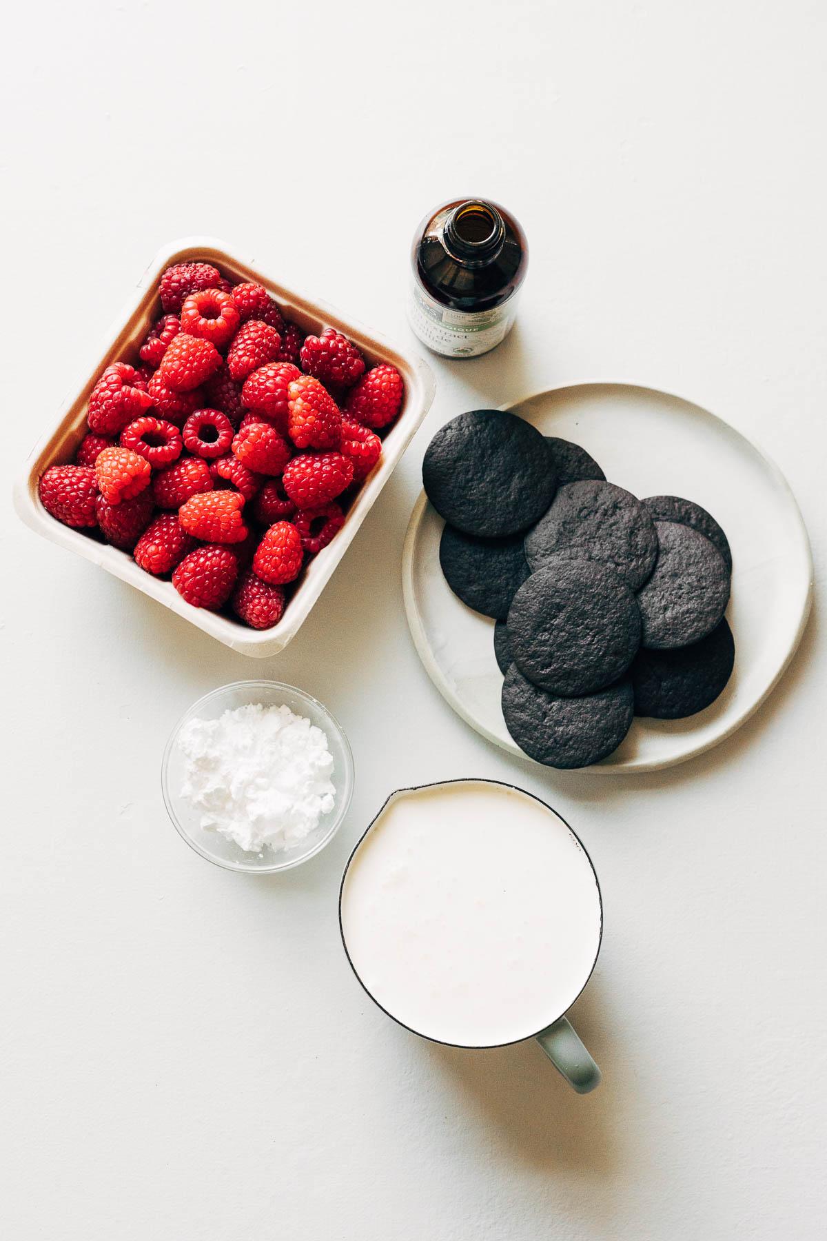 Icebox cake ingredients: fresh raspberries, chocolate wafer cookies, vanilla, cream, and icing sugar.