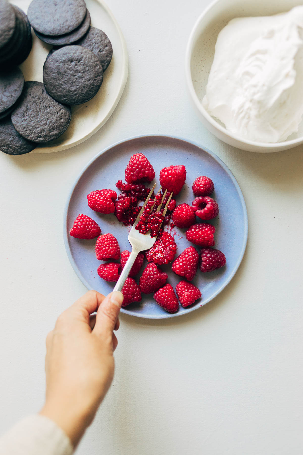 Mashing raspberries with a fork on a plate.