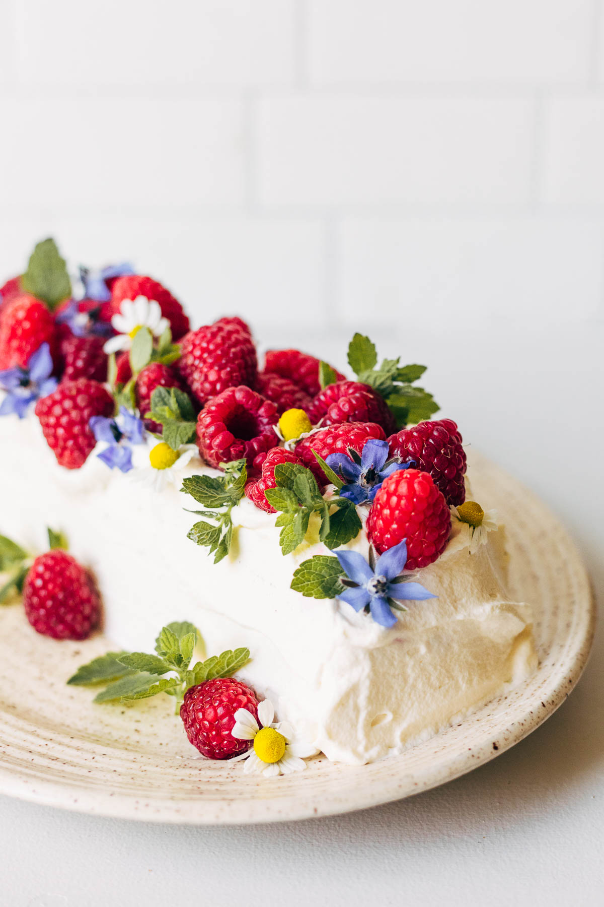 Icebox cake decorated with fresh berries and edible flowers.