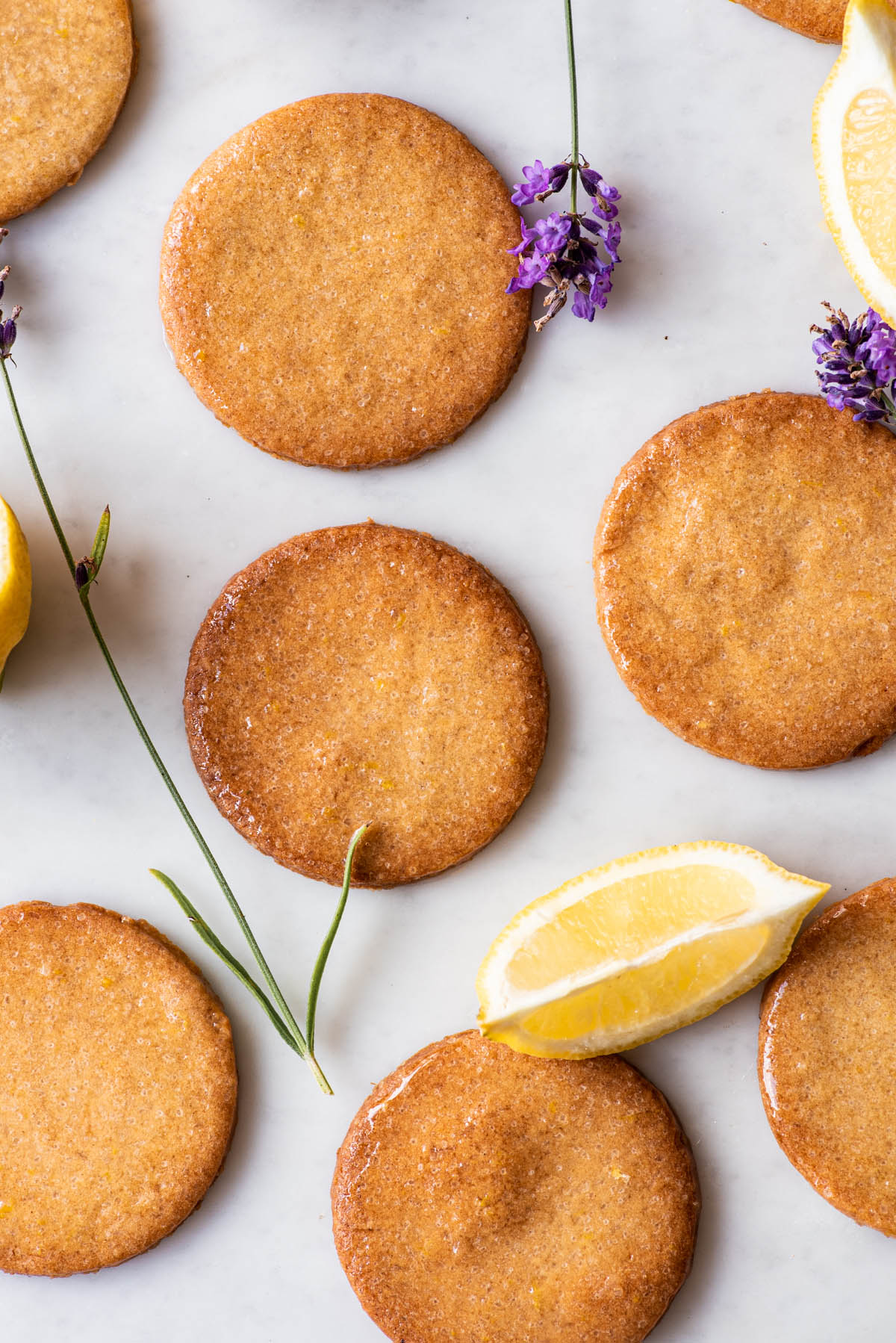 Sugar cookies on a marble surface with lemon slices and lavender sprigs.