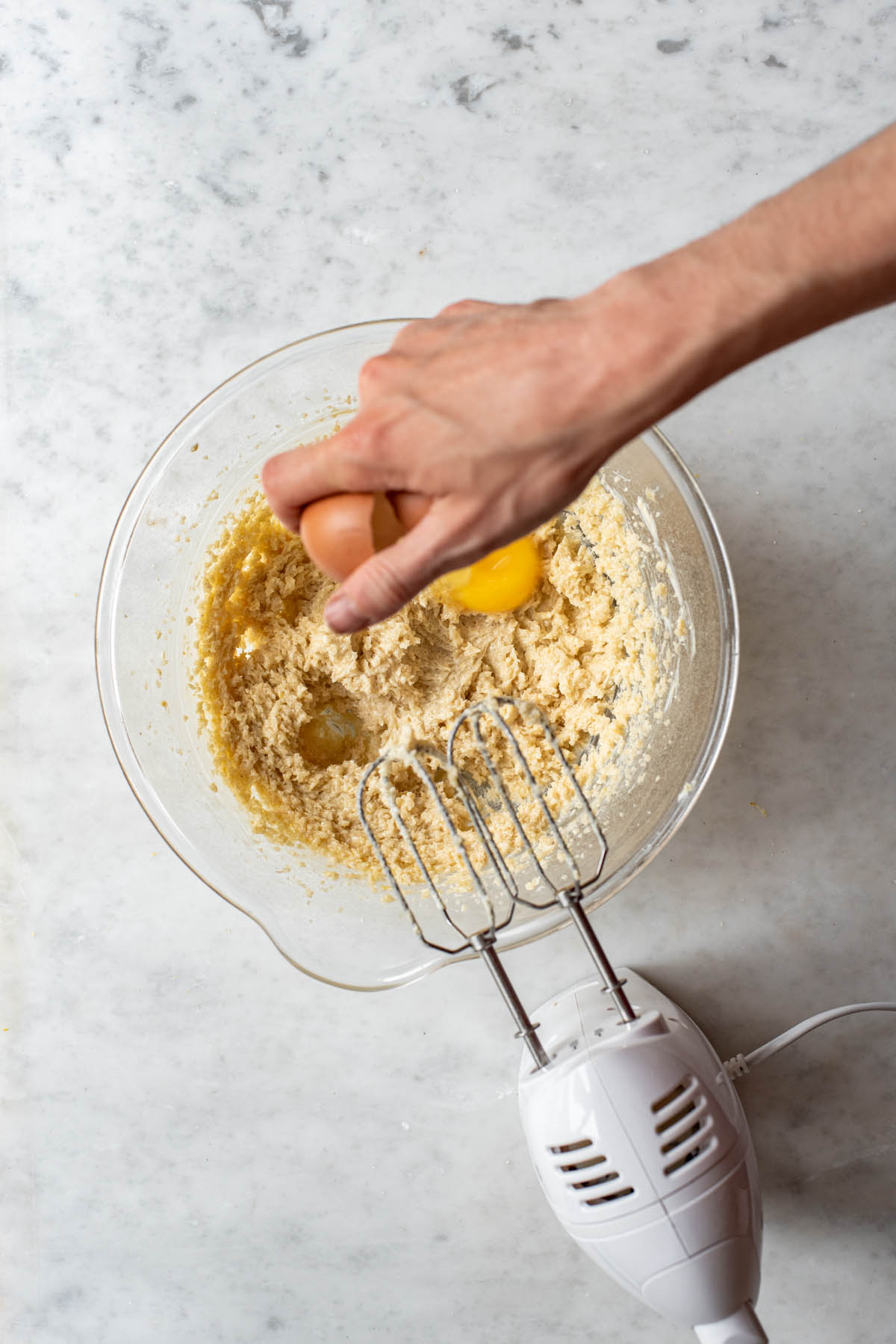 A hand cracking an egg into a glass mixing bowl with cookie dough, and a hand mixer laying nearby.