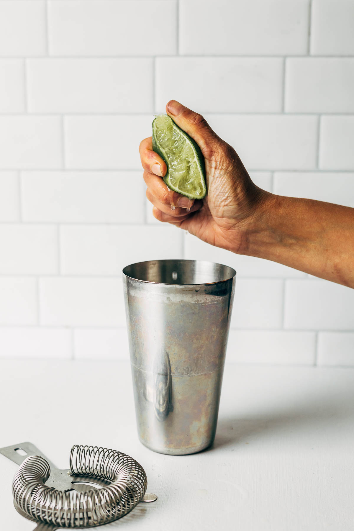 A hand squeezing half of a lime over a metal cocktail shaker.