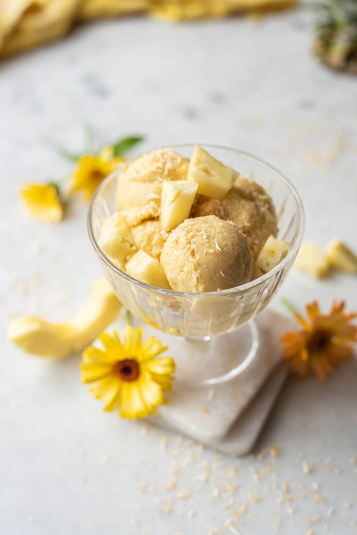 A dish of coconut pineapple ice cream with chunks of fresh pineapple on top and yellow flowers scattered on the marble surface below.