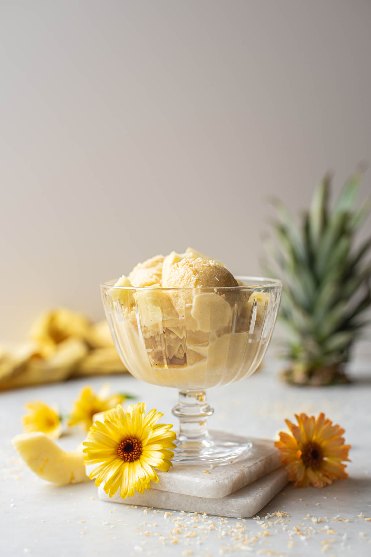 A small glass pedestal dish of coconut pineapple ice cream.