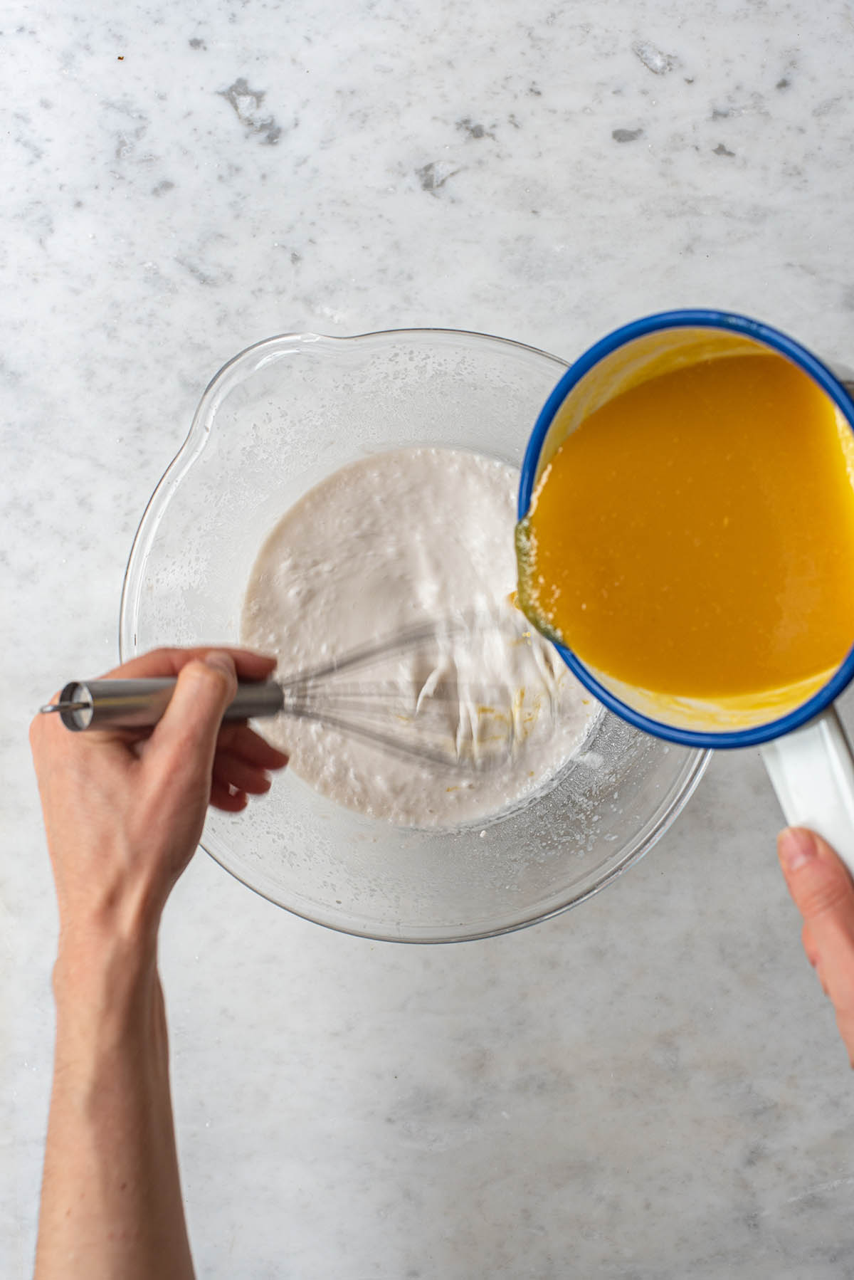 Two hands pouring and whisking yellow liquid from a small white pot into a bowl of whipped coconut milk.