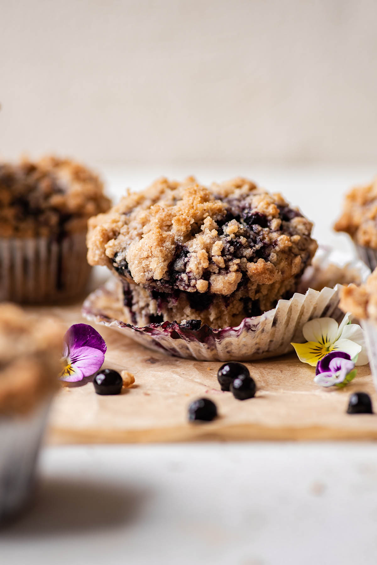 A blueberry streusel muffin with the paper liner folded down.