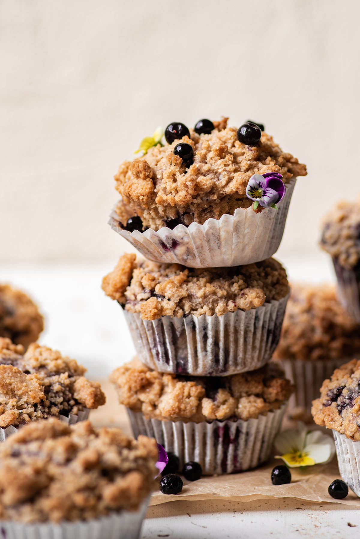 A stack of three blueberry streusel muffins with other muffins surrounding.