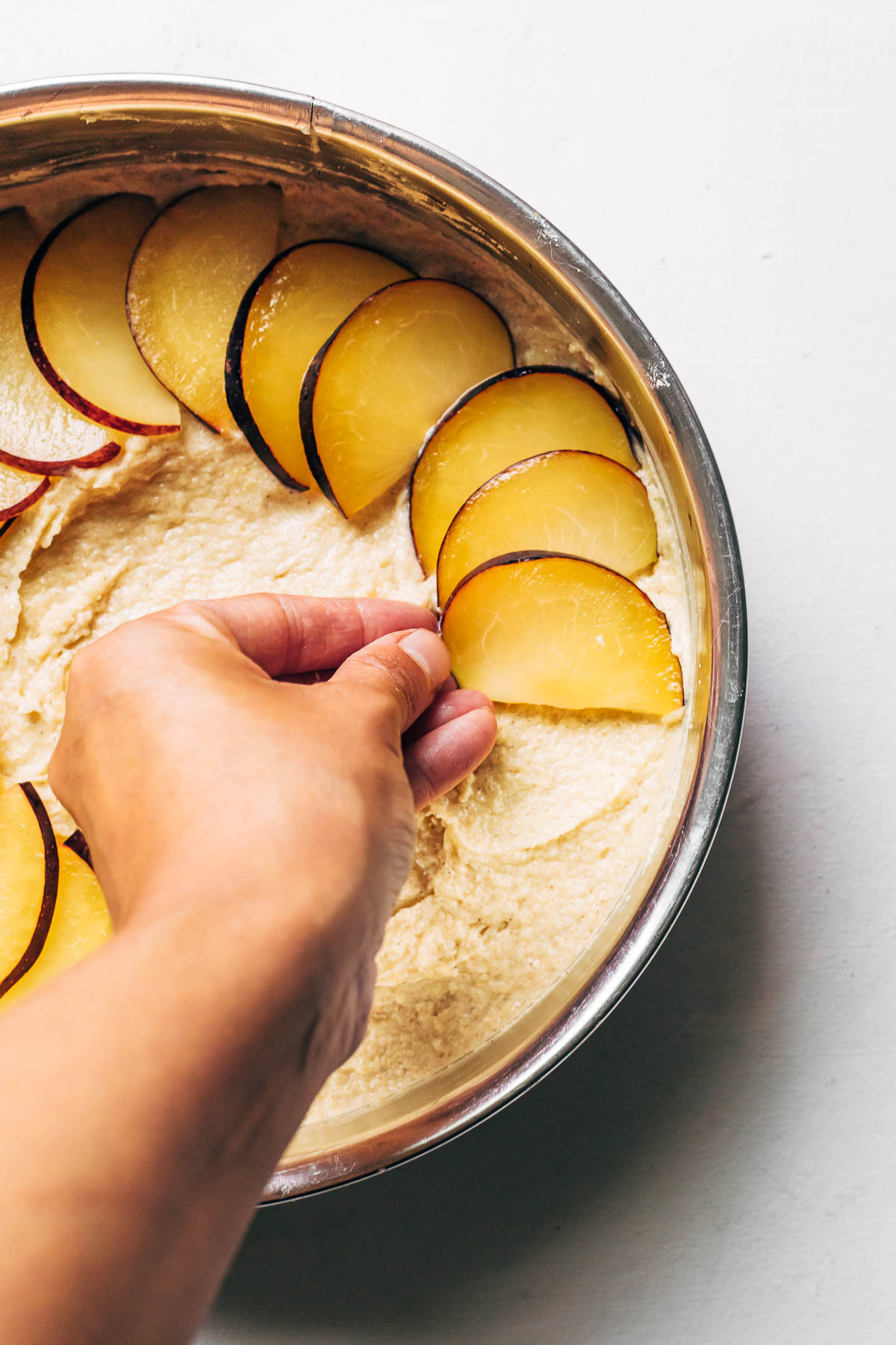 A hand placing a slice of plum on top of cake batter inside a metal cake tin.