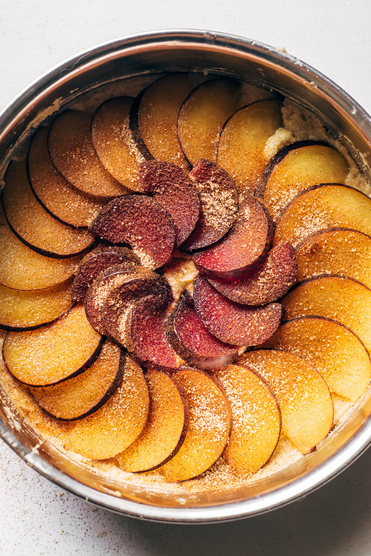 Plums sprinkled with cinnamon sugar in the bottom of a springform pan.