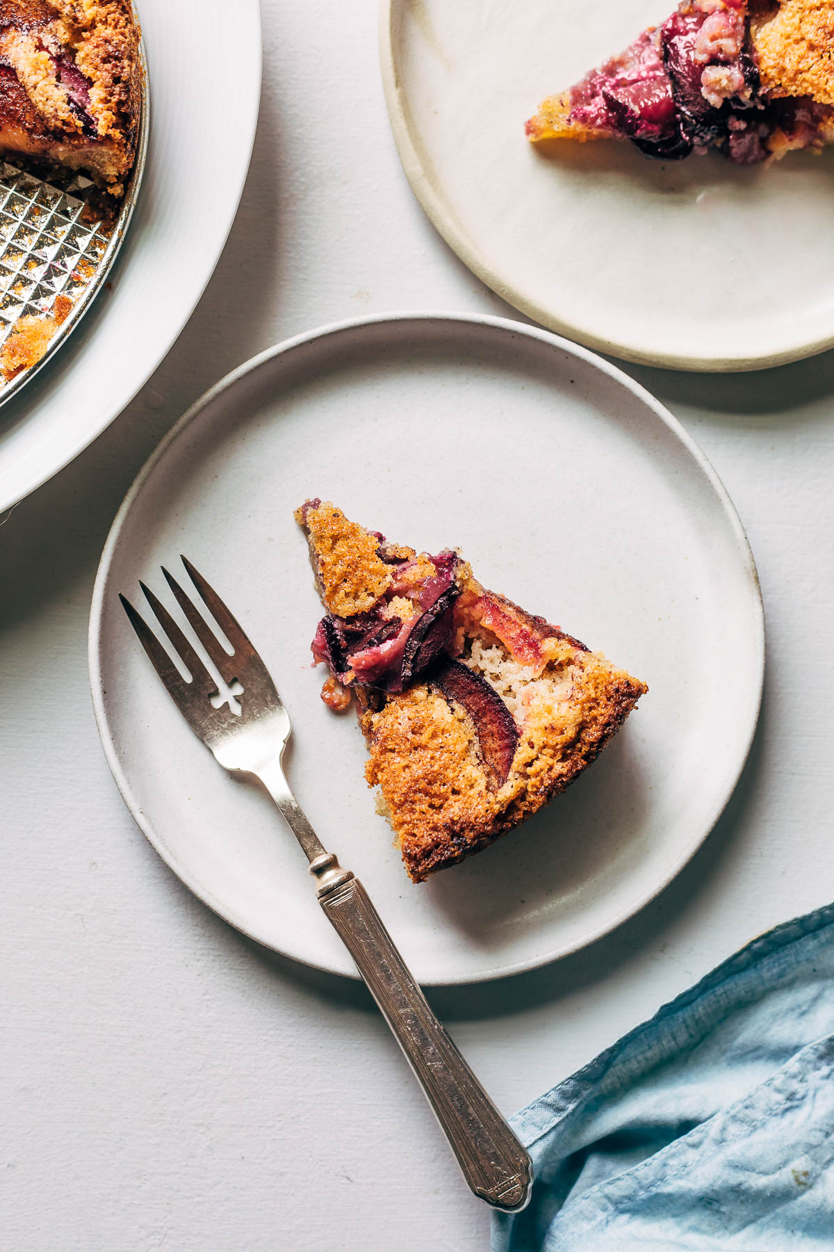 Overhead shot of a slice of gluten-free plum cake on a white plate with a fork and a blue napkin.
