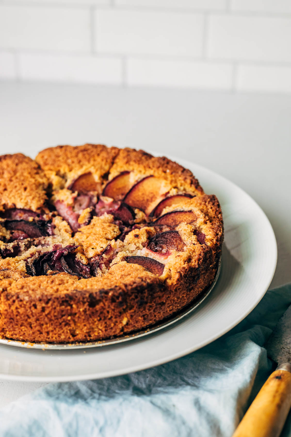 Partial shot of a gluten-free plum cake on a cake stand with a blue napkin underneath and a wood-handled knife.
