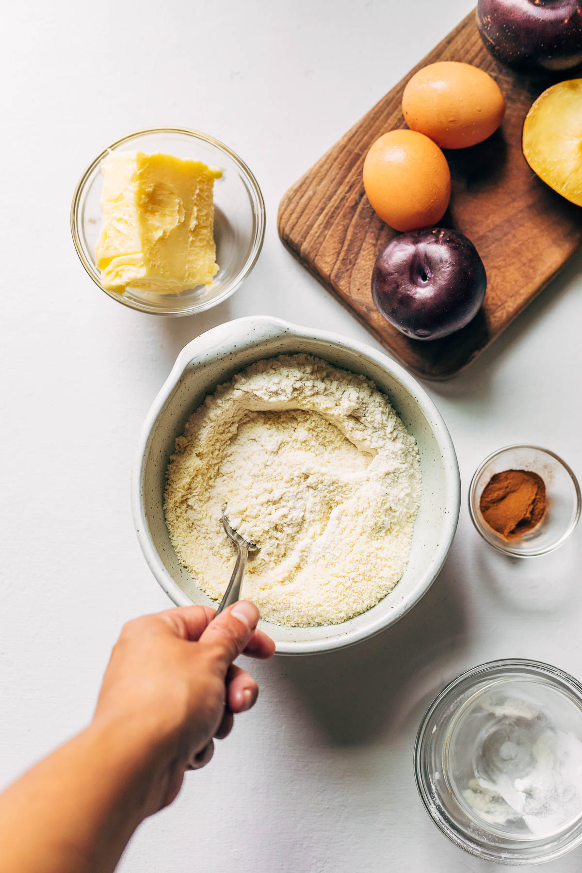 A hand mixing gluten-free flours next to other ingredients to make a plum torte.
