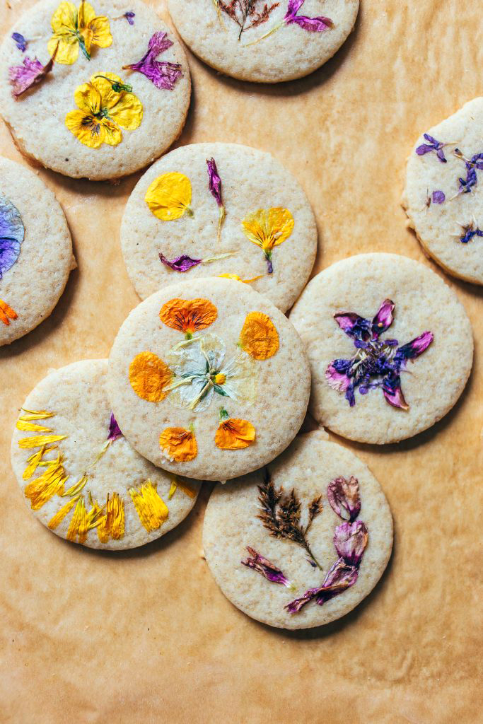 An assortment of flower cookies laid out on brown parchment paper.