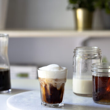 An iced vanilla latte on a round marble board next to jars of ingredients.