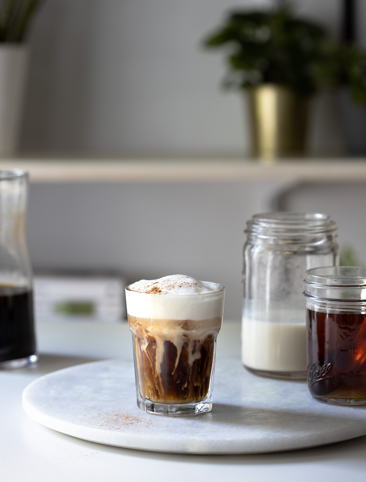 A frothy coffee drink on a round marble board with jars of ingredients nearby.