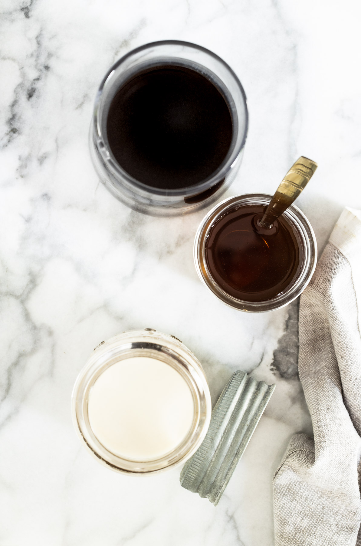 Ingredients to make iced vanilla latte laid out in glass jars on a marble surface.