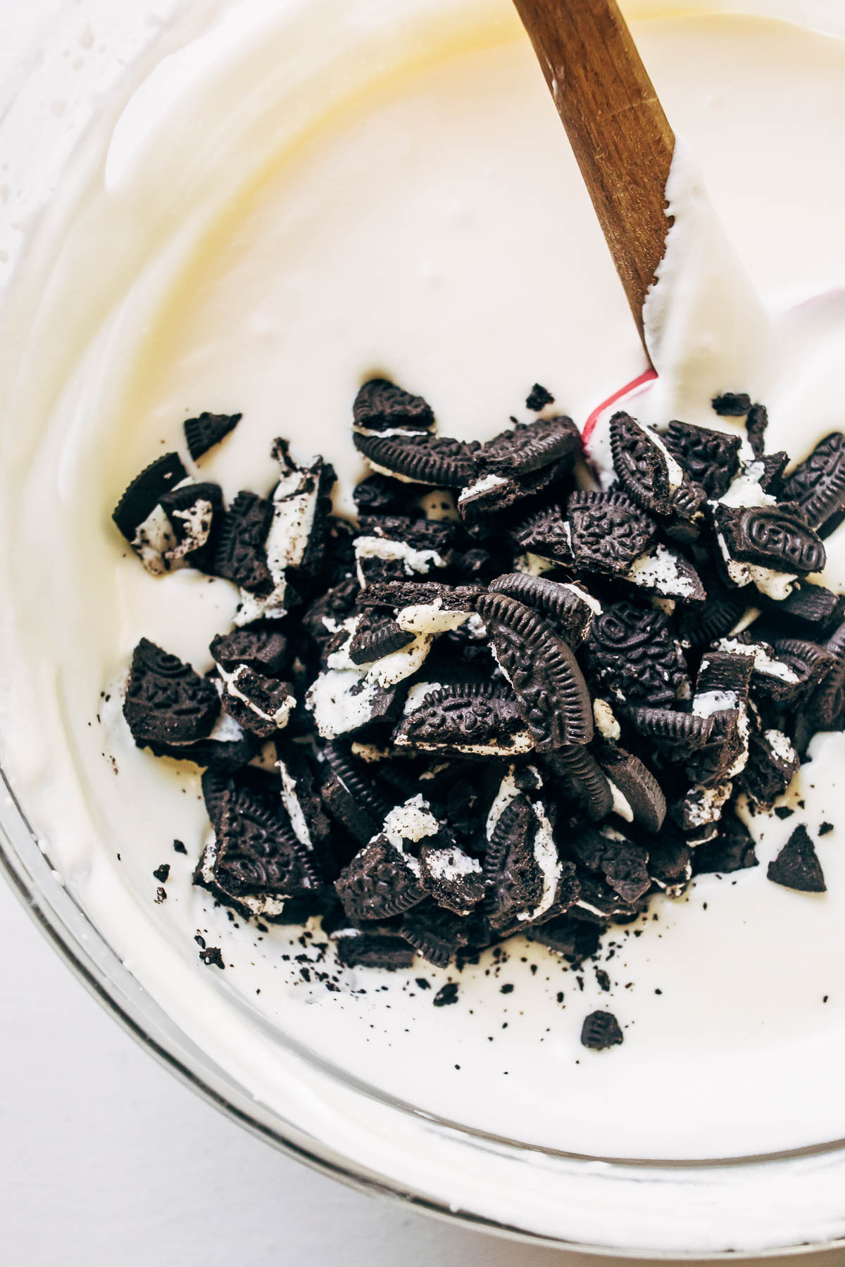 Crushed Oreo cookies in a bowl of white ice cream batter.