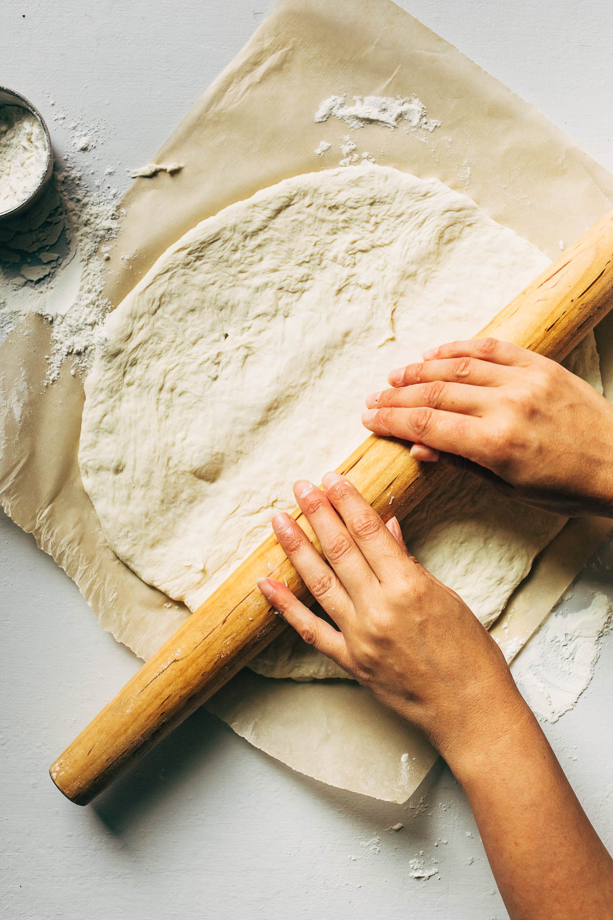 Hands rolling pizza dough on brown parchment paper.