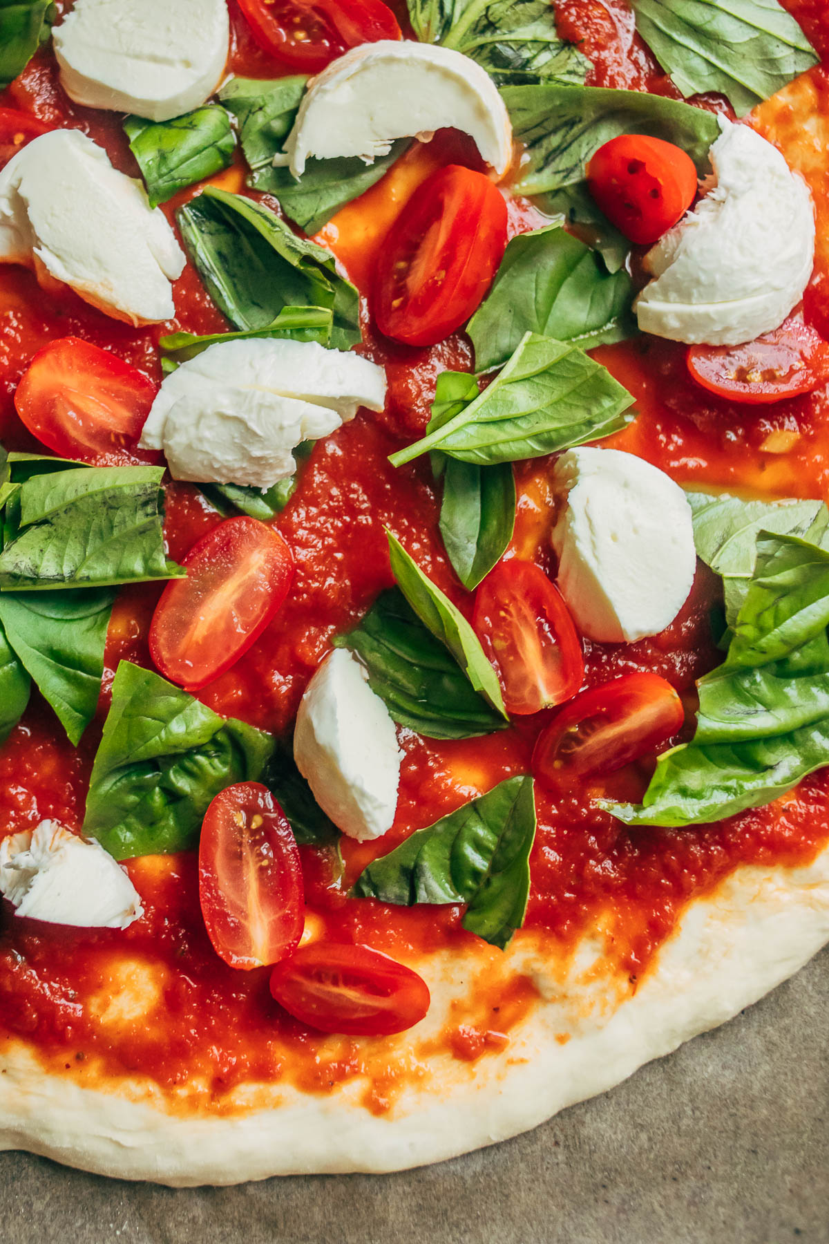 Uncooked pizza topped with tomato sauce, tomatoes, bocconcini, and fresh basil.