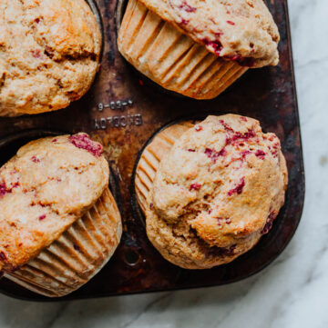 A pan of buttermilk muffins with raspberries.