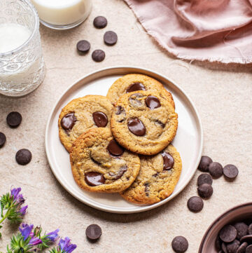 A plate of chocolate chip cookies on a stone surface with a pink linen, glasses of milk, scattered chocolate chips, and purple flowers nearby.