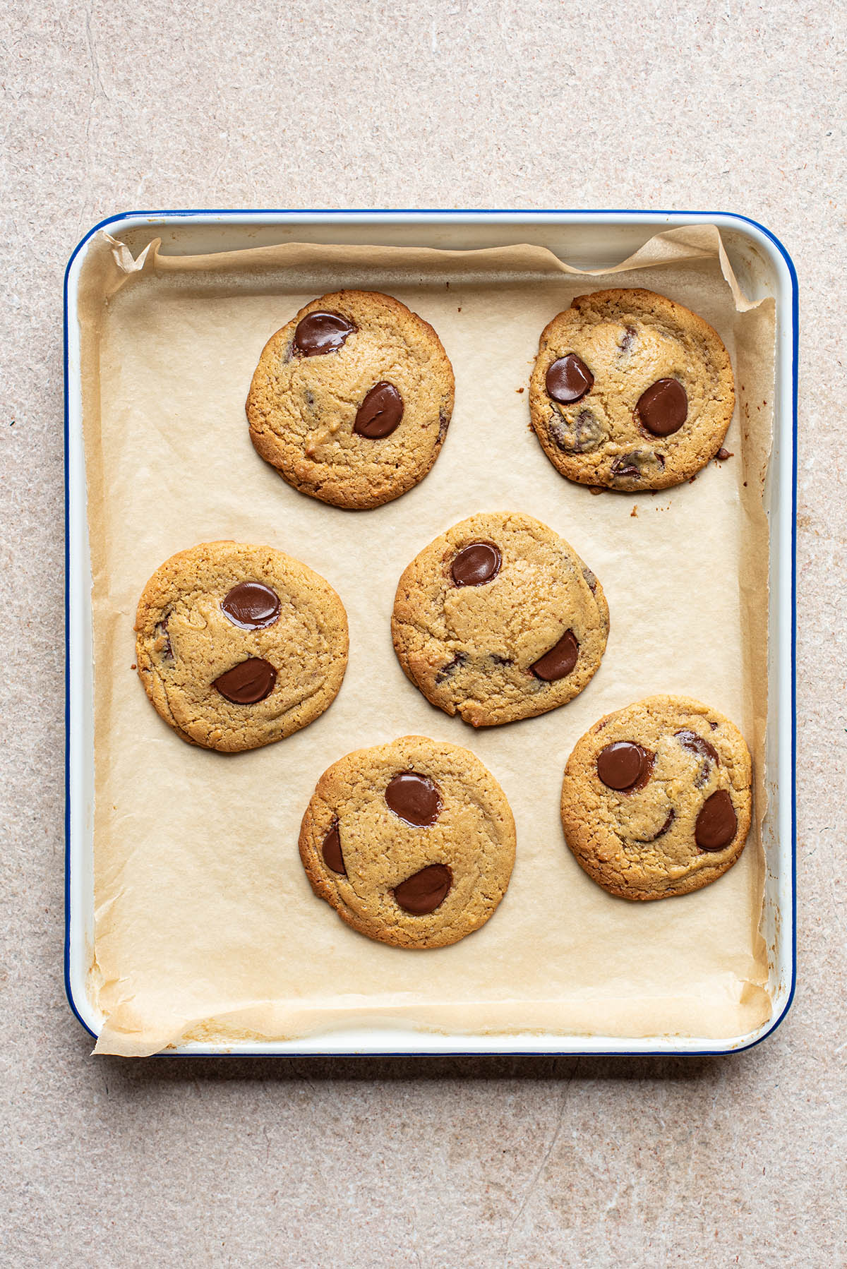 Six small batch chocolate chip cookies on a parchment paper-lined baking sheet.
