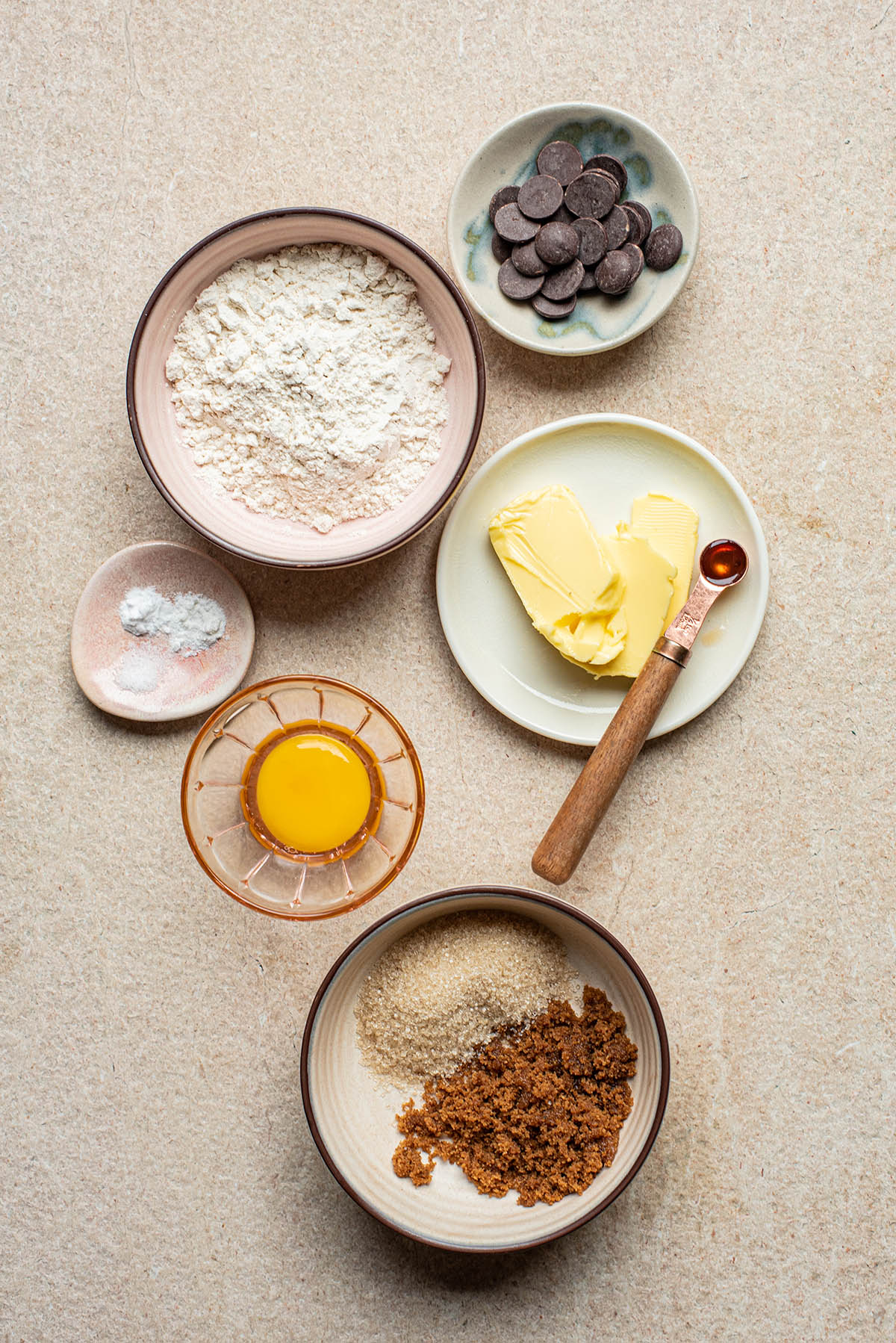 Overhead image of chocolate chip cookie ingredients laid out in small bowls on a stone surface.