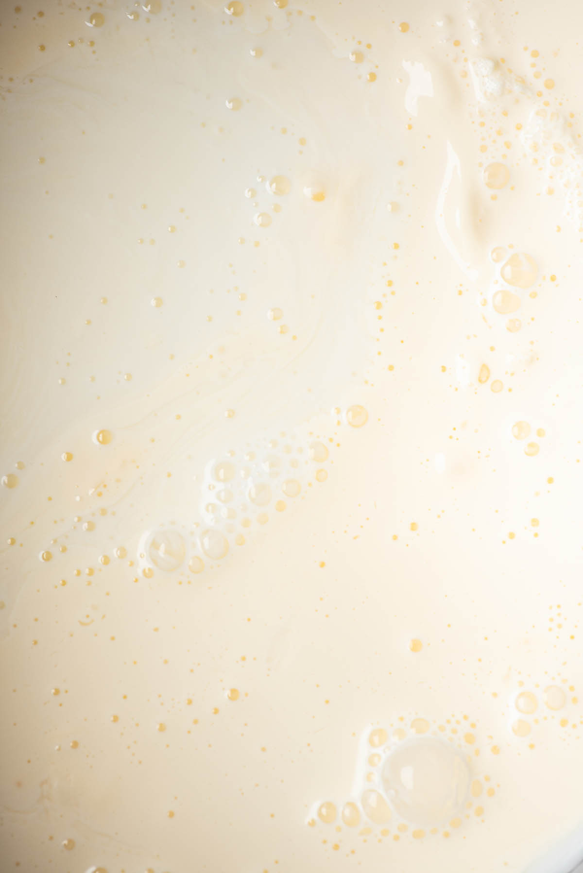 Close up of milk and cream mixing together.