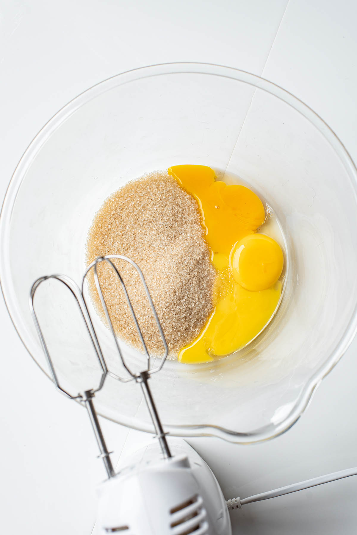 Egg yolks and sugar in a large glass bowl.