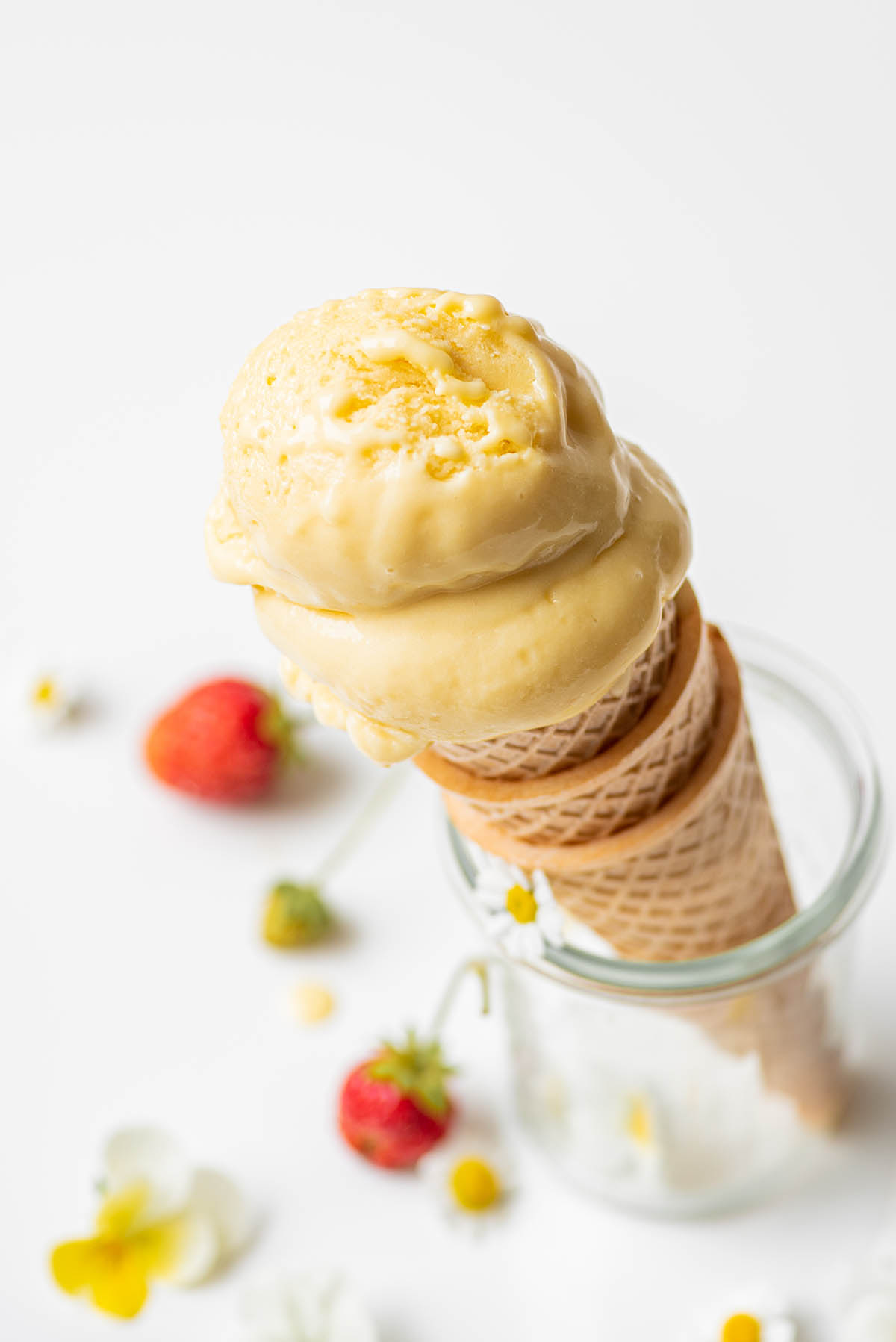 Close up of two scoops of ice cream on a stack of cones.