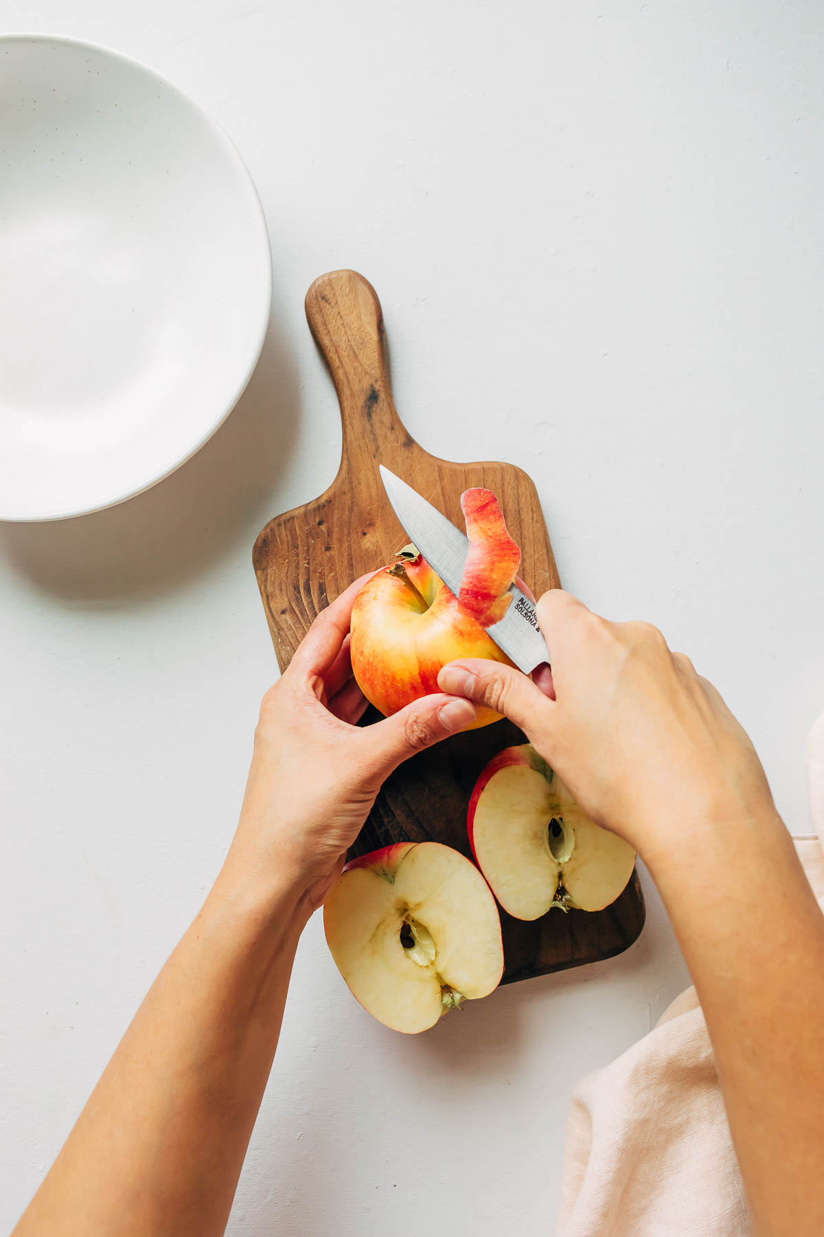 hands peeling an apple with a paring knife.