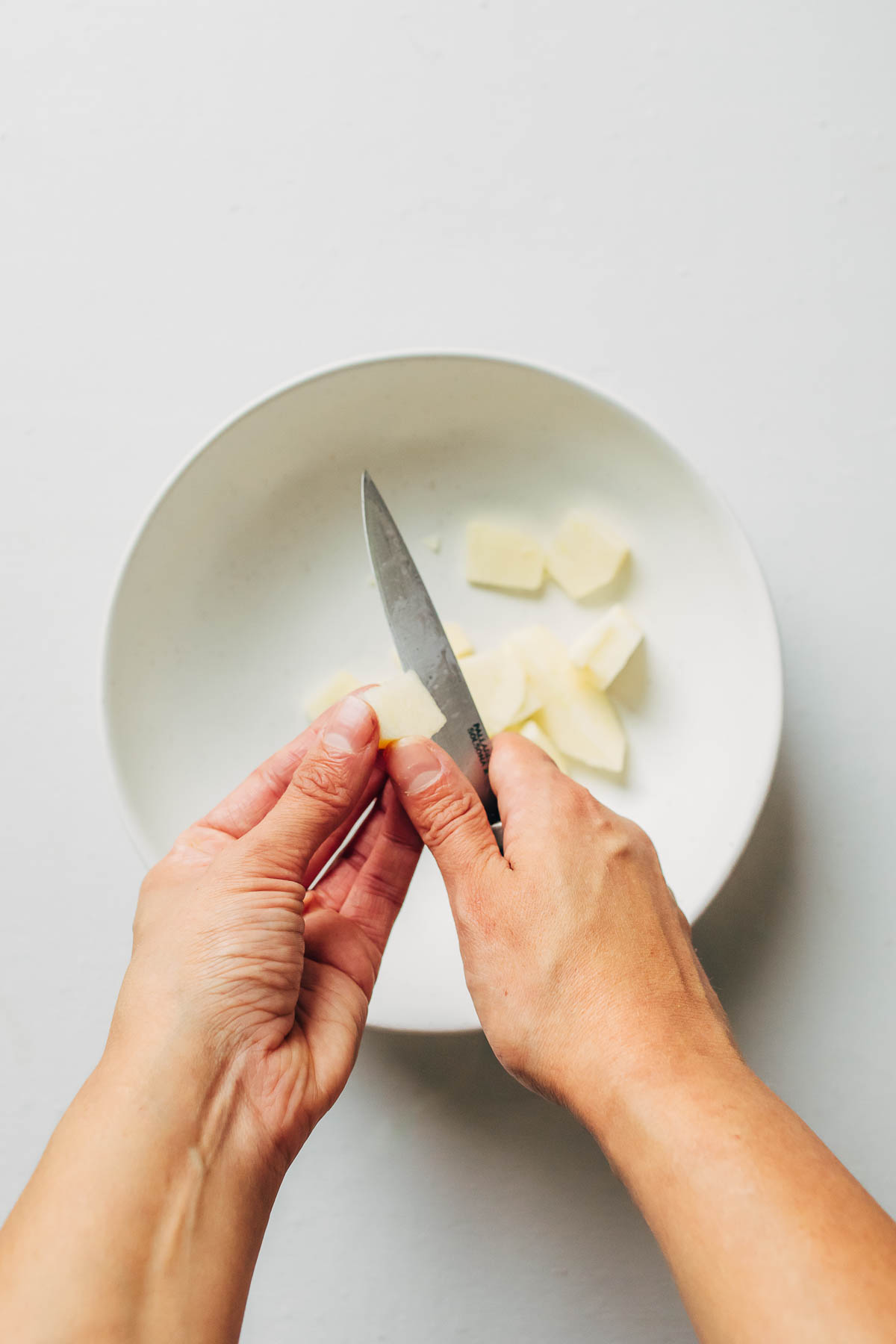 A hand slicing apples into a small bowl using a paring knife.