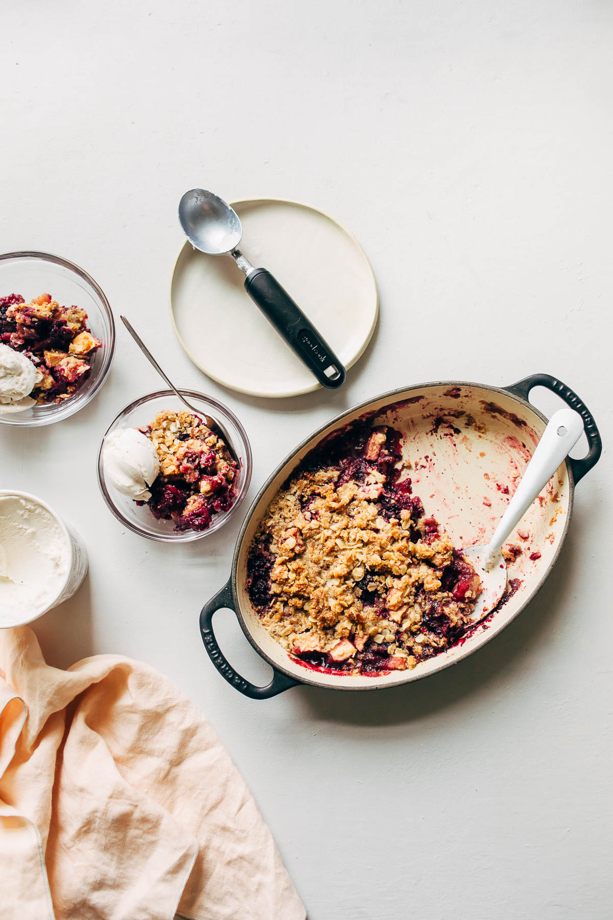 A pan of blackberry and apple crisp, and two bowls of crisp topped with ice cream, on a white surface.