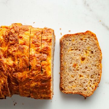 A sliced apple cheddar loaf on a marble surface.