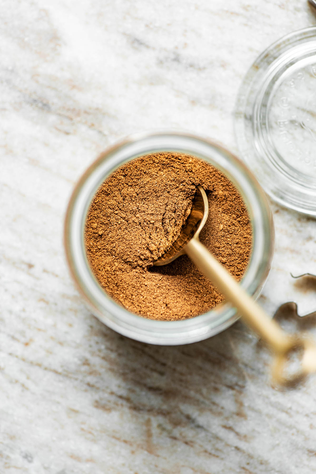 Spice mix in a small glass jar with a spoon in it, top down view.